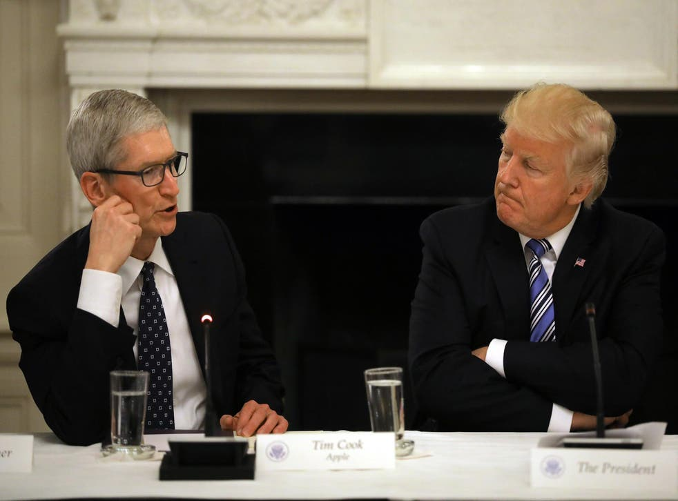 US President Donald Trump listens as Tim Cook, CEO of Apple speaks during an American Technology Council roundtable at the White House in Washington