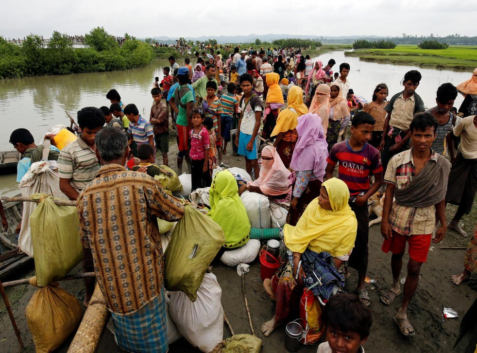 Rohingya refugees are seen waiting for a boat to cross the border through the Naf river in Maungdaw, Burma