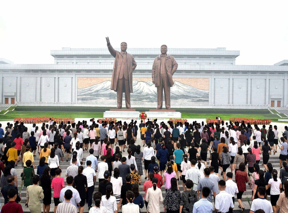 North Korean residents offer flowers before the statues of Kim Il-Sung and Kim Jong-Il during celebrations of the 69th anniversary of North Korea's founding