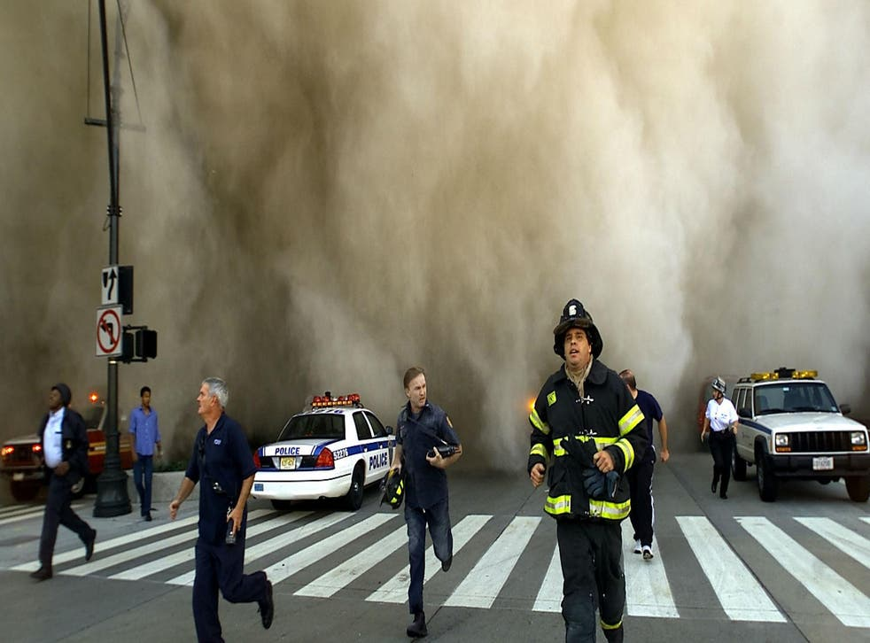 Policemen and firemen run away from the huge dust cloud caused as the World Trade Center's Tower One collapses after terrorists crashed two hijacked planes into the twin towers, 11 September, 2001 in New York City. Picture: