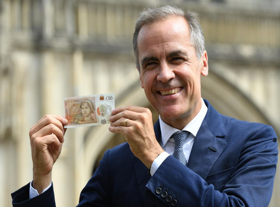 Bank of England governor Mark Carney holds the new, devalued, £10 note