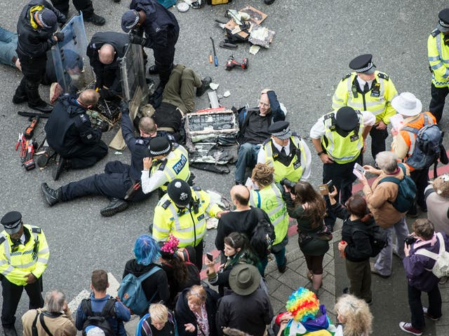 <p>Police work to remove protesters who blocked an access road to the 2017 Defence and Security Equipment International (DSEI) arms fair by chaining themselves together on 6 September 2017</p>