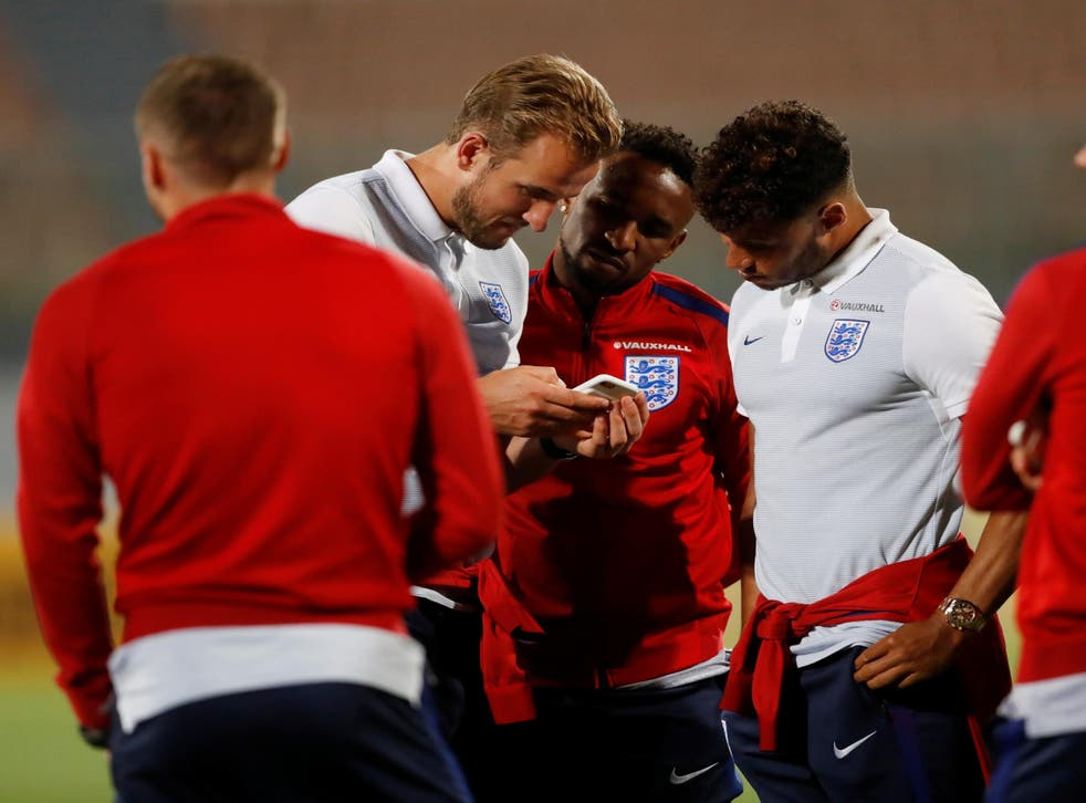 England's Alex Oxlade-Chamberlain, Harry Kane and Jermain Defoe look at a mobile phone during the stadium visit