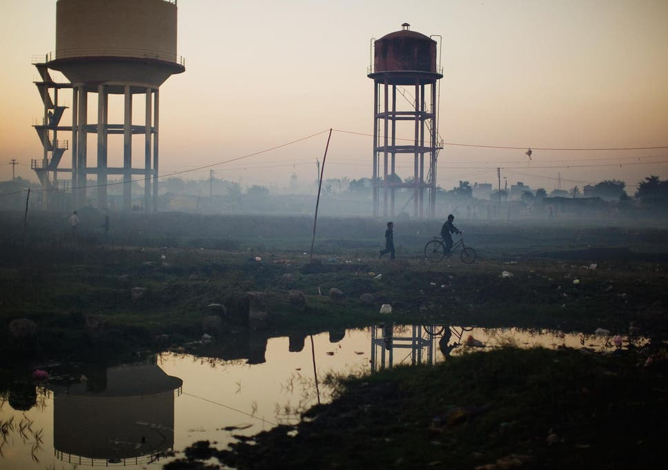 Children play near water towers in front of their homes near the Union Carbide factory in Bhopal, India
