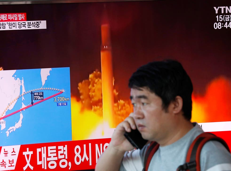 A television broadcasts a news report on North Korea firing a missile that flew over Japan's northern Hokkaido island