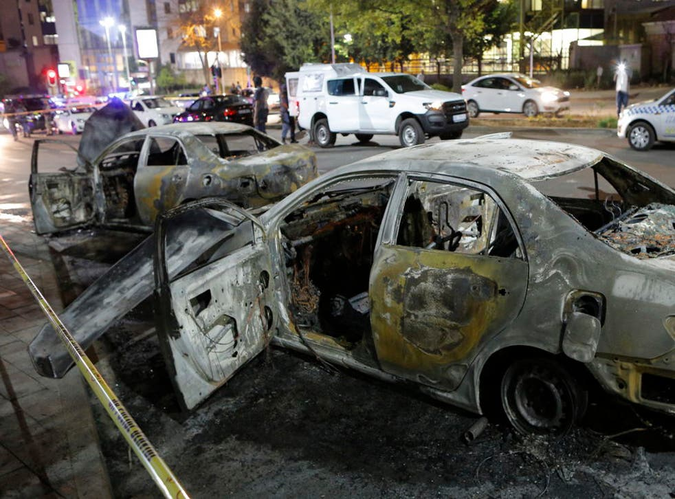 The burned out remains of two taxis are seen behind a police cordon after clashes broke out between metered taxi drivers and Uber taxi drivers this week in the northern suburb of Sandton