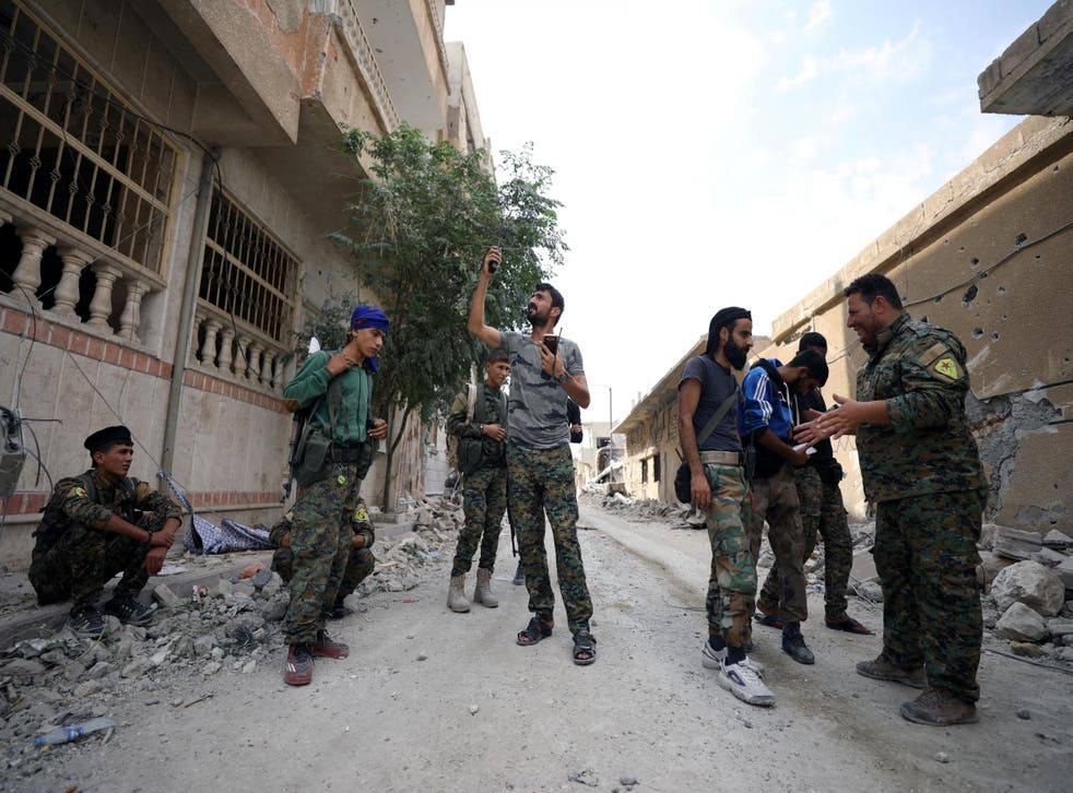 A fighter from the SDF tries to communicate on a radio amid the rubble of a damaged street in Raqqa this month Reuters
