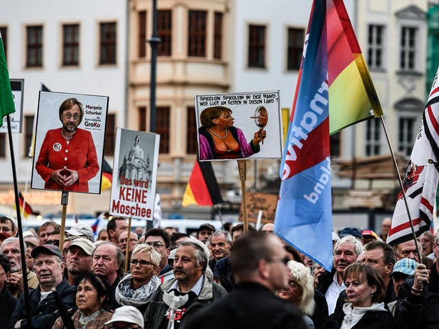 Supporters of the 'Pegida' movement and German right-wing populist party Alternative für Germany (AfD) hold banners at a rally in Dresden