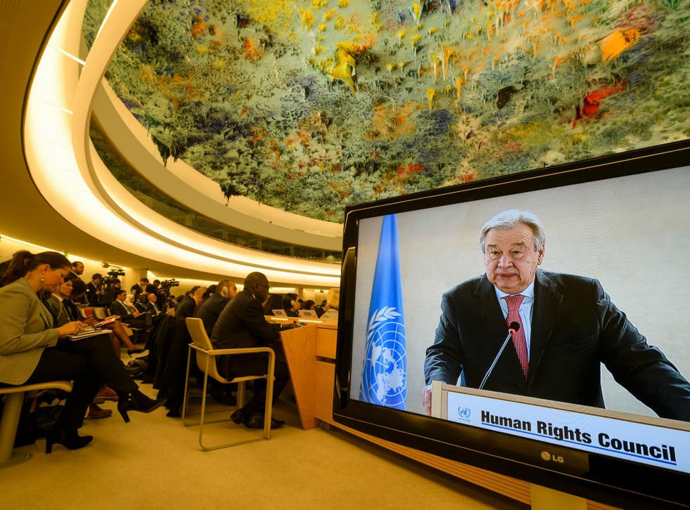 UN Secretary-General Antonio Guterres is seen on a TV screen while addressing the United Nations Human Rights Council in Geneva. Nine members of the Council have been found as human rights violators.