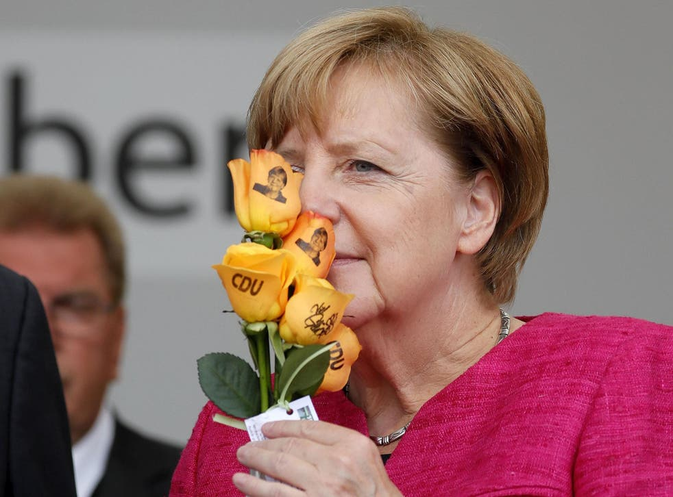 Angela Merkel smells some Christian Democratic Union (CDU) branded flowers at an election campaign event in Heppenheim