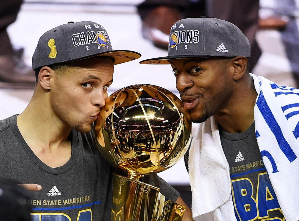 Stephen Curry (l) and Andre Iguodala celebrate with the NBA championship trophy in 2015