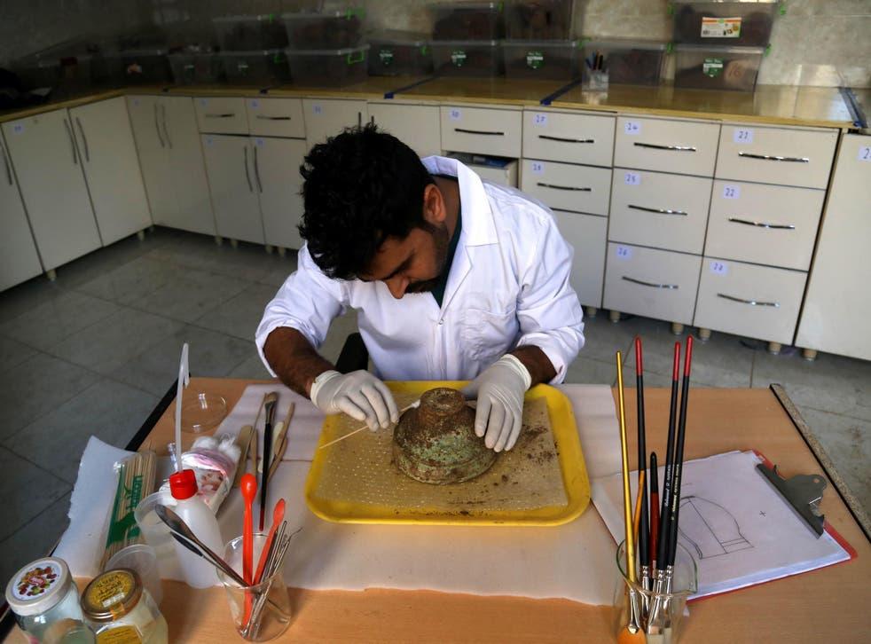 An archaeologist cleans an Assyrian bowl discovered in Iraqi Kurdistan.