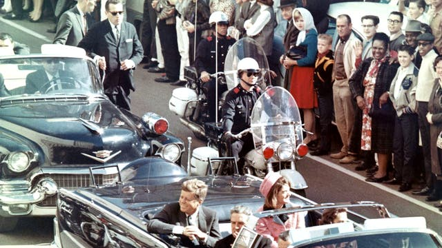 President John F. Kennedy and his wife Jacqueline Kennedy ride with secret agents in an open car motorcade shortly before the assassination, 22 November 1963