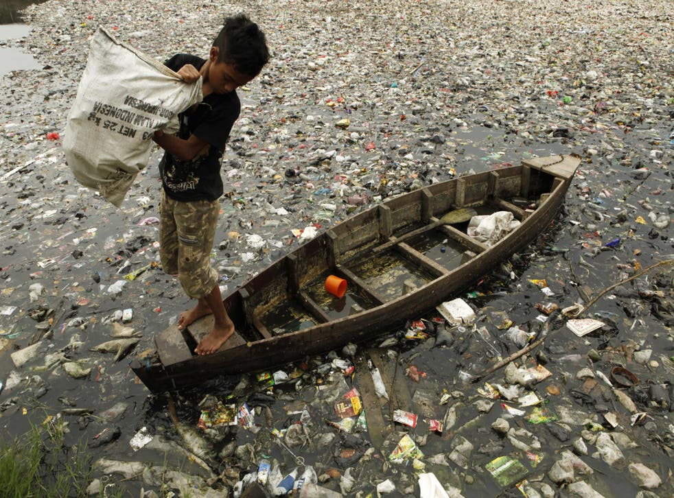 A child collects plastic cups from a polluted river in Jakarta