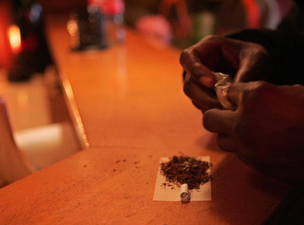 A customer rolls a joint at a coffeeshop in Rosendaal, a Dutch town where the mayor has taken the controversial decision to shut down four such cannabis cafés