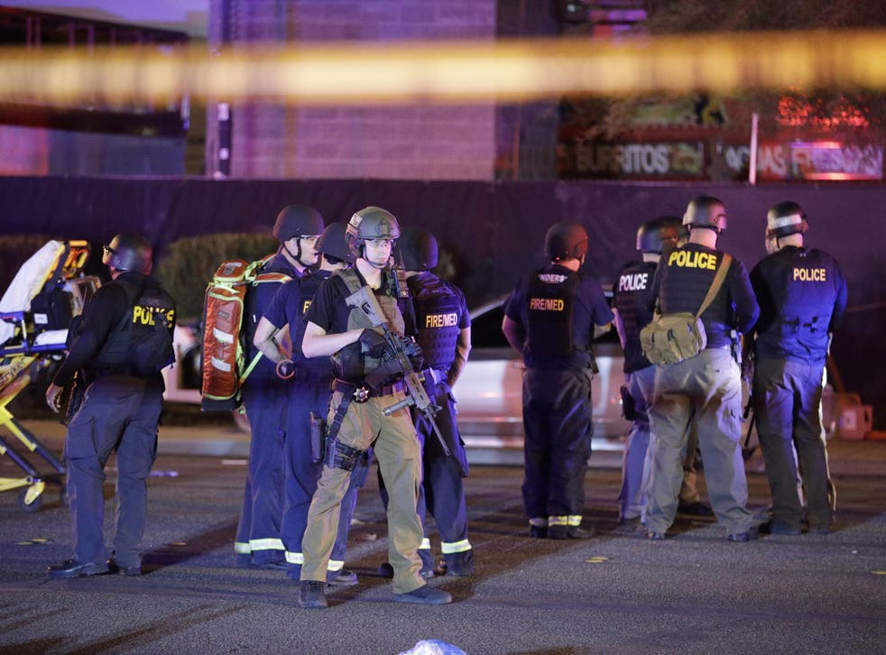 Police officers and medical personnel stand at the scene of a shooting near the Mandalay Bay resort and casino on the Las Vegas Strip.