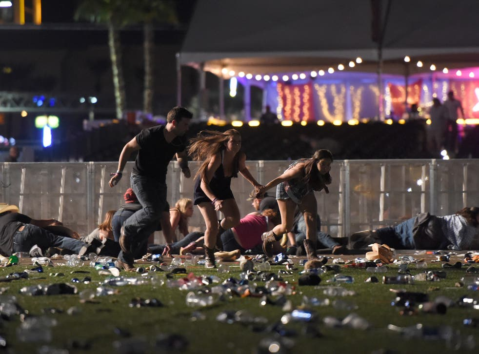 People run from the Route 91 Harvest country music festival in Las Vegas after a shooter opened fire