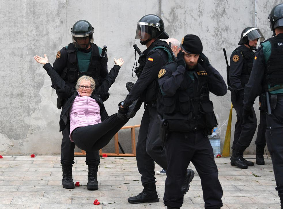 Police carry away an elderly woman after she tried to vote at a polling station in Catalonia