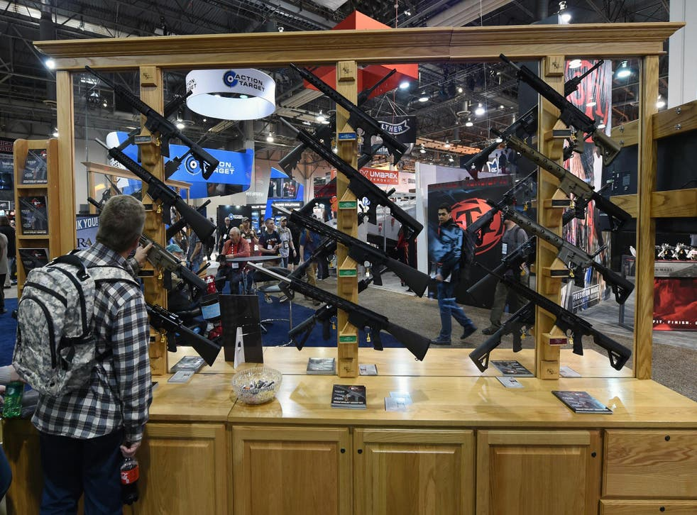 A convention attendee looks at rifles displayed at the Rock River Arms booth at the 2016 SHOT Show in Las Vegas