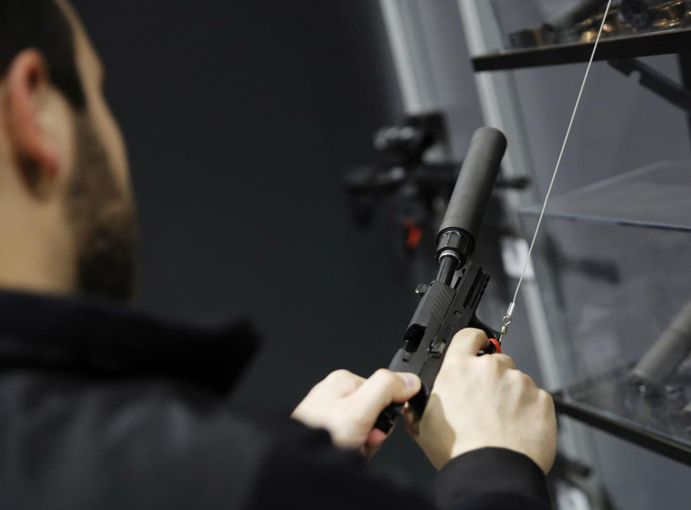 A visitors pulls the slide of a pistol with a silencer at a gun displays at a National Rifle Association outdoor sports trade show on 10 February 2017 in Harrisburg, Pennsylvania