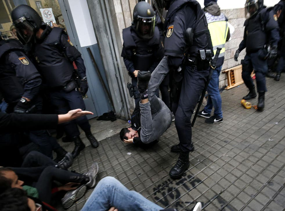 Spanish police officers drag a man from a polling station in Barcelona