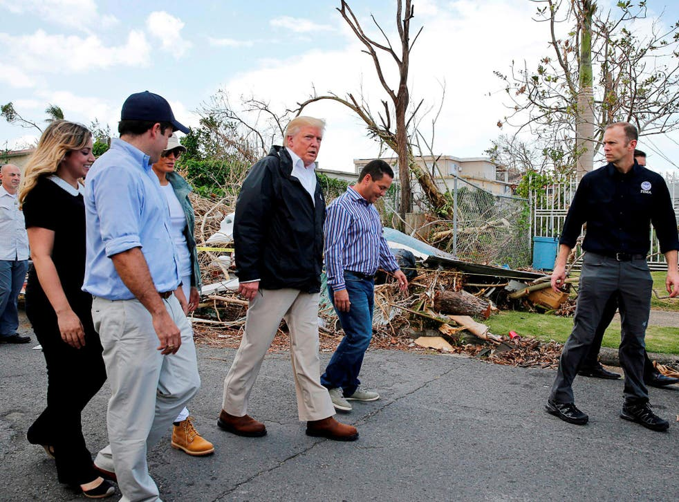 US President Donald Trump walks past hurricane wreckage as he participates in a walking tour with First Lady Melania Trump, Guaynabo Mayor Angel Perez Otero (second right) and Acting FEMA Administrator Brock Long (far right) as well as Puerto Rico Governor Ricardo Rossello (left) and his wife Beatriz Areizeaga in areas damaged by Hurricane Maria