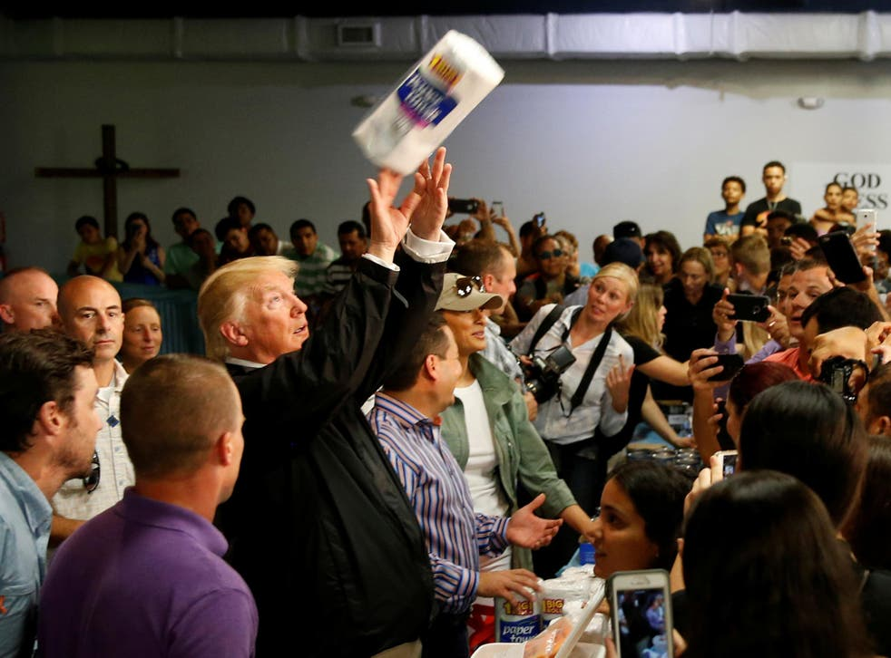 US President Donald Trump tosses rolls of paper towels to people at a hurricane relief distribution centre at Calvary Chapel in San Juan