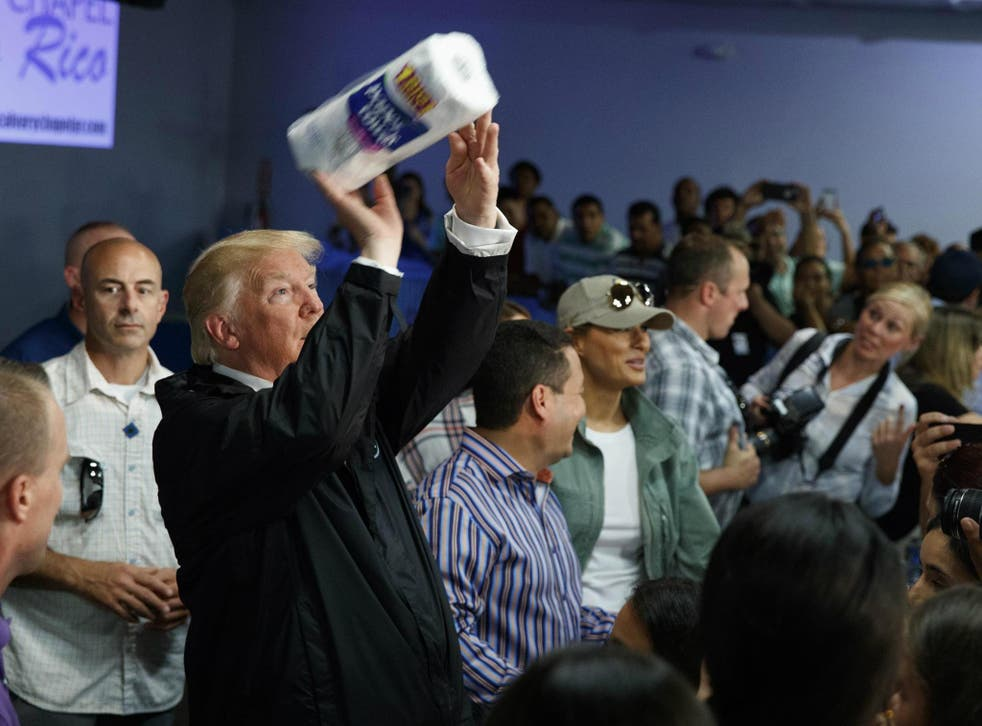 President Donald Trump tosses paper towels into a crowd as he hands out supplies at Calvary Chapel, 3 October, in Guaynabo, Puerto Rico.