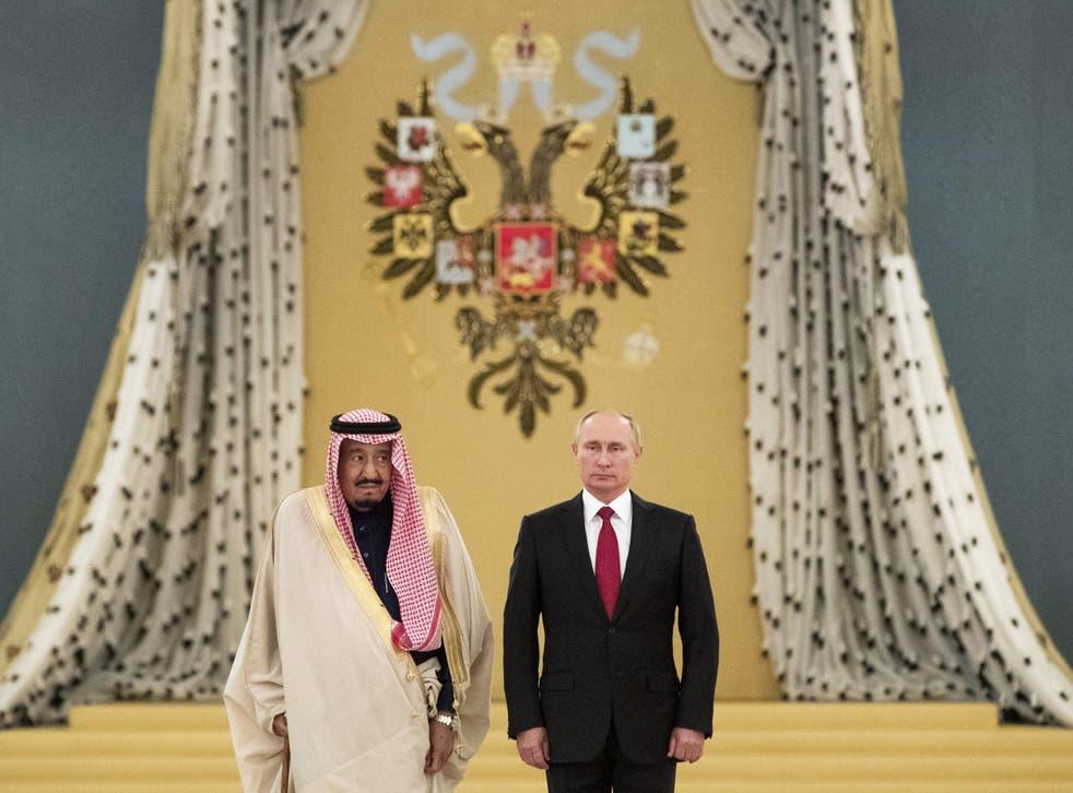 Saudi King Salman bin Abdulaziz and Russian President Vladimir Putin listen to national anthems during their meeting at the Kremlin