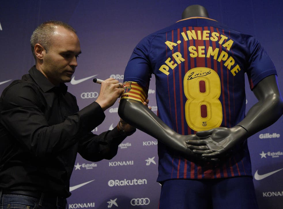 Andres Iniesta signs a shirt saying 'Iniesta forever'