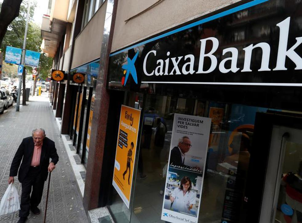 A man walks past a Caixa bank branch in Barcelona, Spain October 6, 2017. REUTERS/Yves Herman