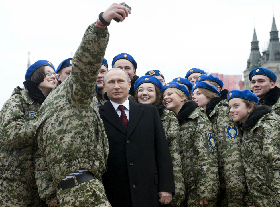 Russian Prime Minister Vladimir Putin poses for a selfie with members of a youth military patriotic club in 2015