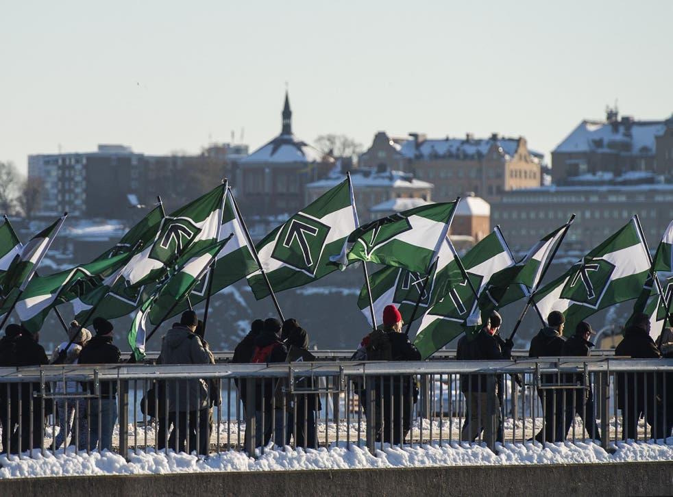 Nordic Resistance Movement supporters marching with flags bearing their 'Tyr rune' logo