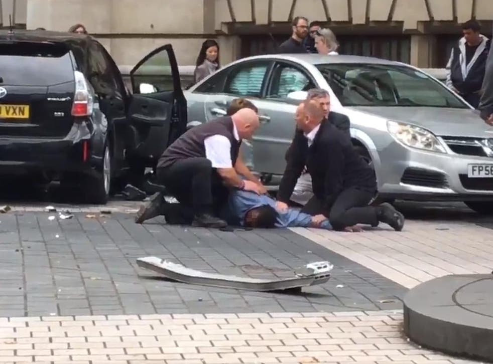 Police pin down a man, believed to be the driver, following the accident outside the museum