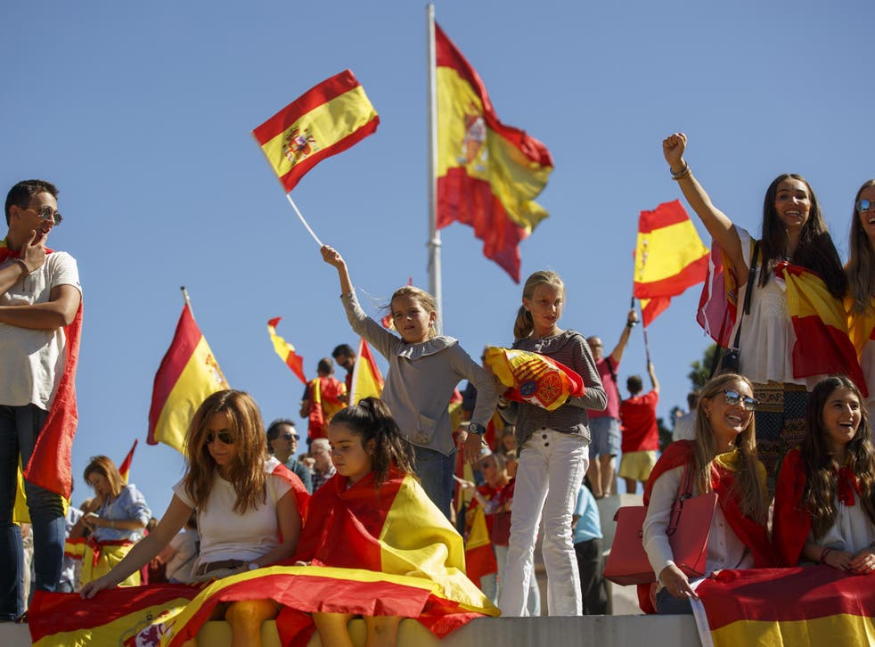 Pro-unity demonstrators hold Spanish flags during the rally called by the DANAES foundation at Colon Square in Madrid