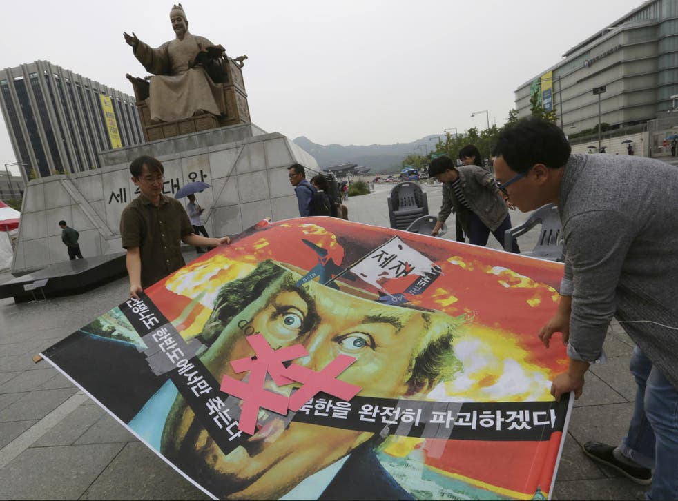 South Korean protesters carry a caricature of Donald Trump during a rally to denounce the US' policy against North Korea, near the American Embassy in Seoul on 26 September