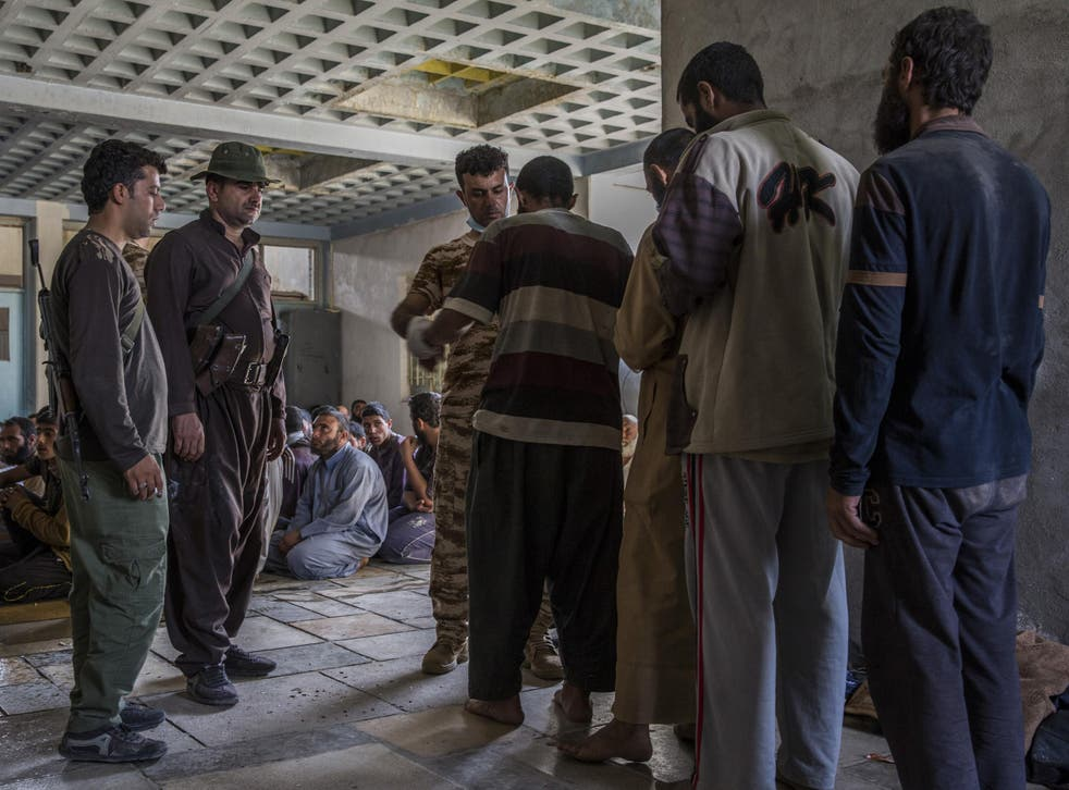 Men suspected of being Isisfighters are searched at a security screening centre near Kirkuk, Iraq