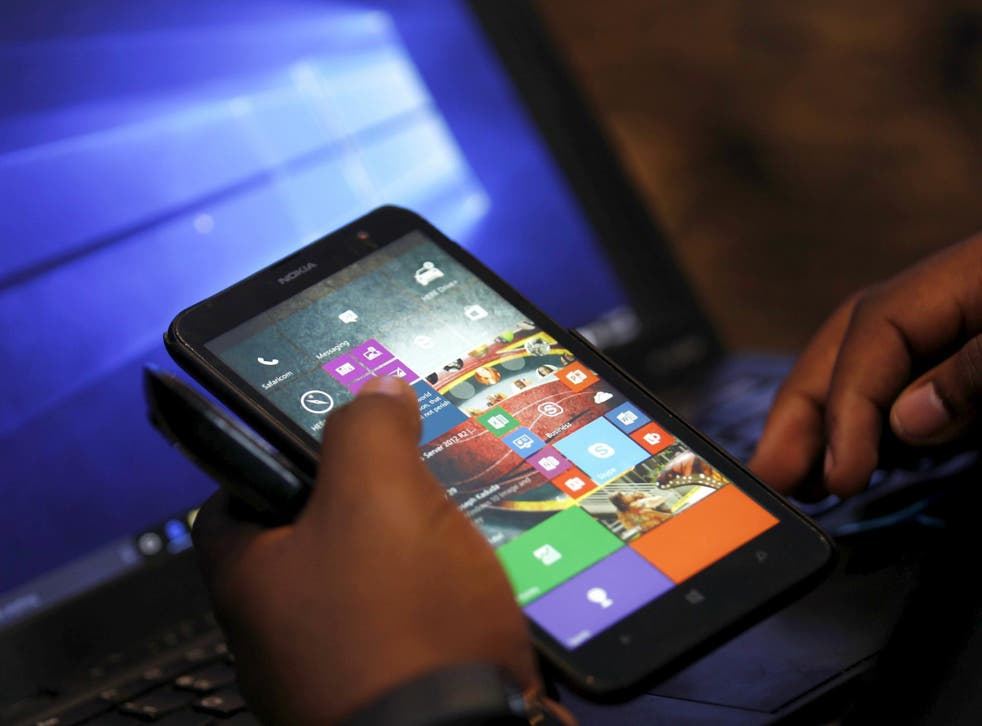 A Microsoft delegate checks applications on a smartphone during the launch of the Windows 10 operating system in Kenya's capital Nairobi, July 29, 2015