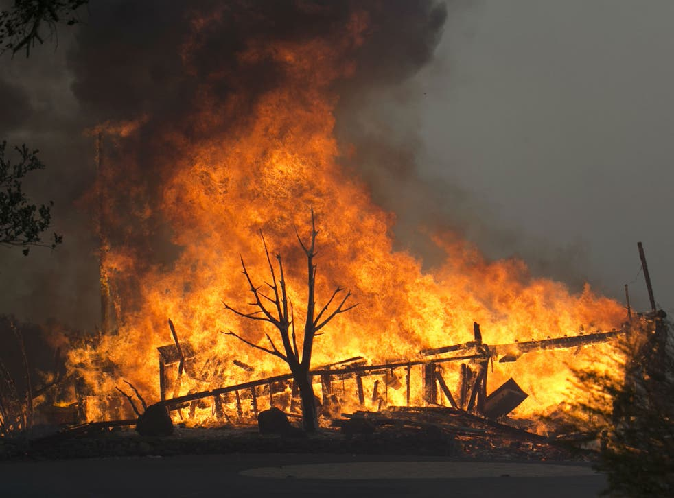 Flames from a wildfire consume a home Monday, Oct. 9, 2017, east of Napa, Calif
