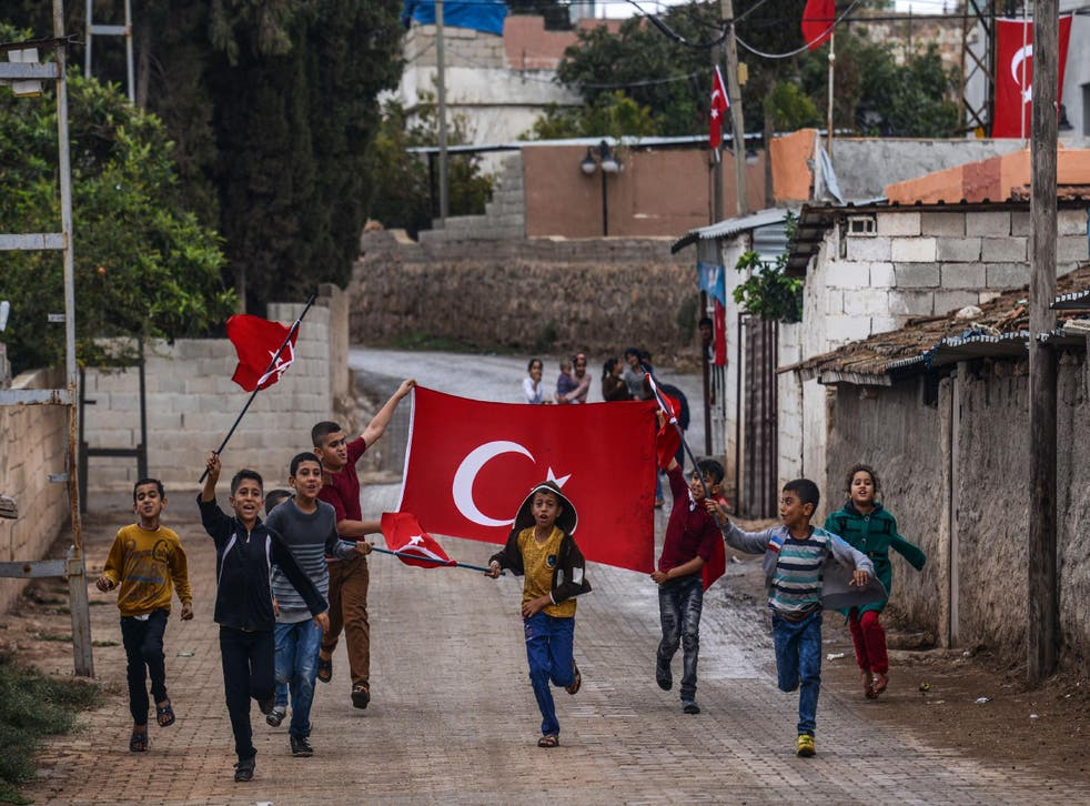 Turkish children run with national flags as they gesture towards army vehicles near the Turkey-Syria border in Reyhanli, Hatay province, on 9 October 2017