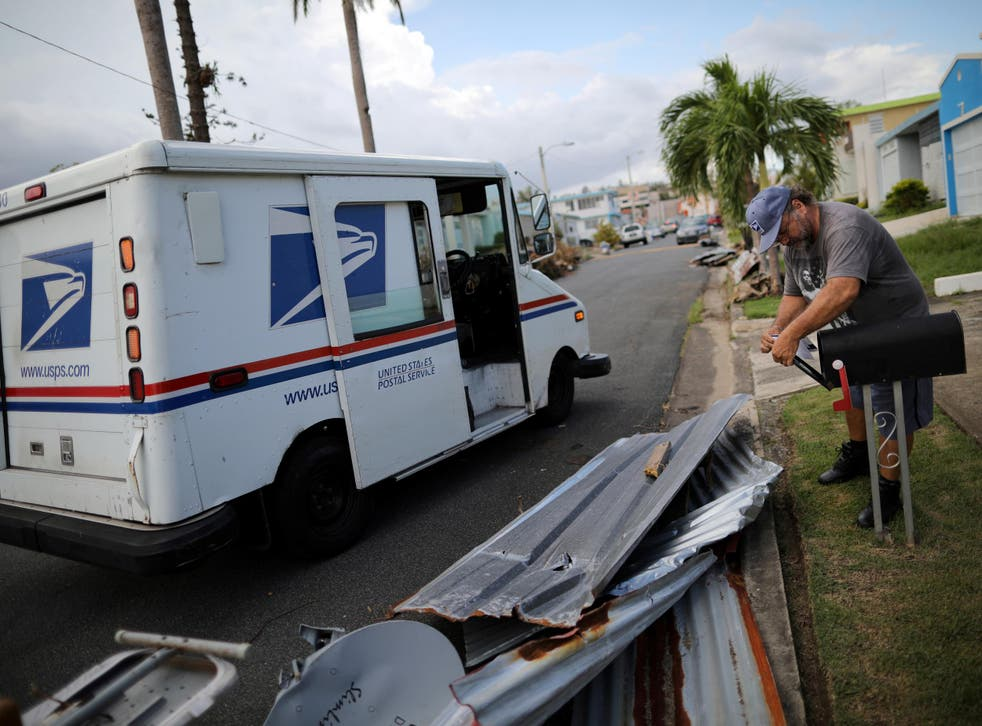 Alfredo Martinez, a postman for the US Postal Service delivers the mail at an area damaged by Hurricane Maria in San Juan, Puerto Rico