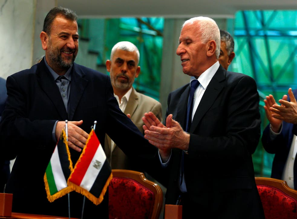 Head of Hamas delegation Saleh Arouri, and Fatah negotiator Azzam Ahmad, sign a reconciliation deal in Cairo, Egypt, on 12 October 2017