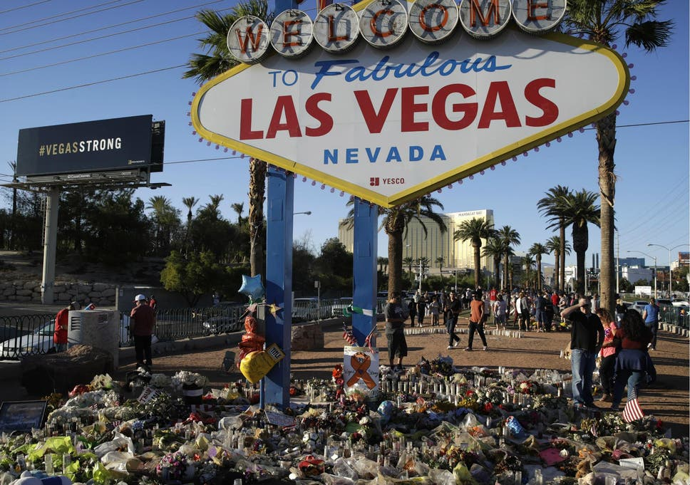Flowers, candles and other items surround the famous Las Vegas sign at a makeshift memorial