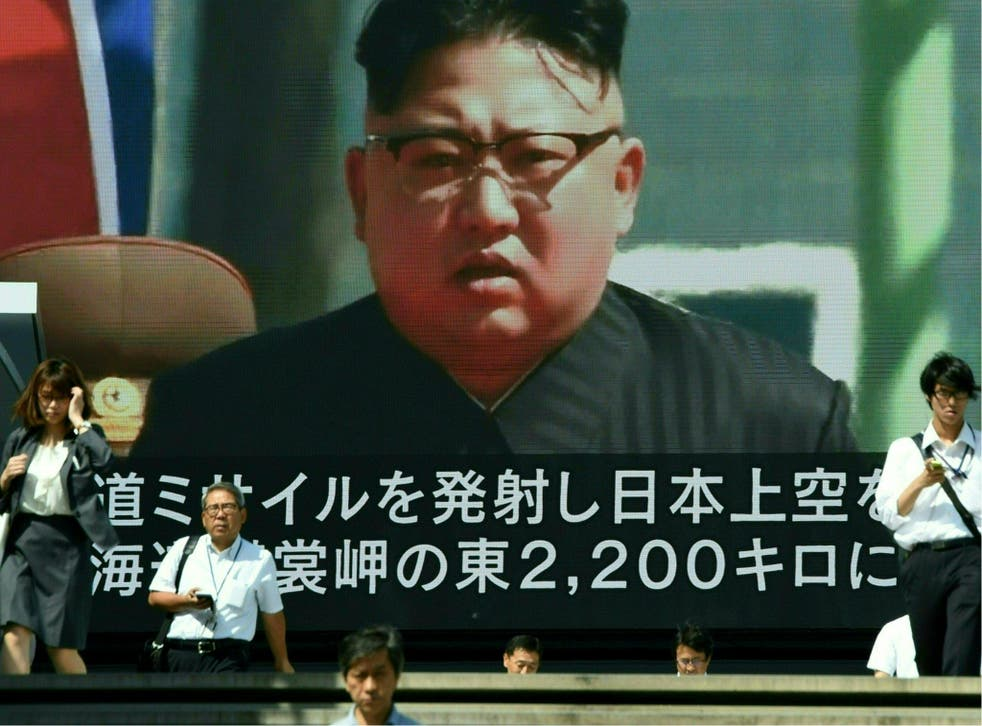 Pedestrians walk in front of a large video screen in Tokyo broadcasting a news report showing North Korean leader Kim Jong-Un (File photo)