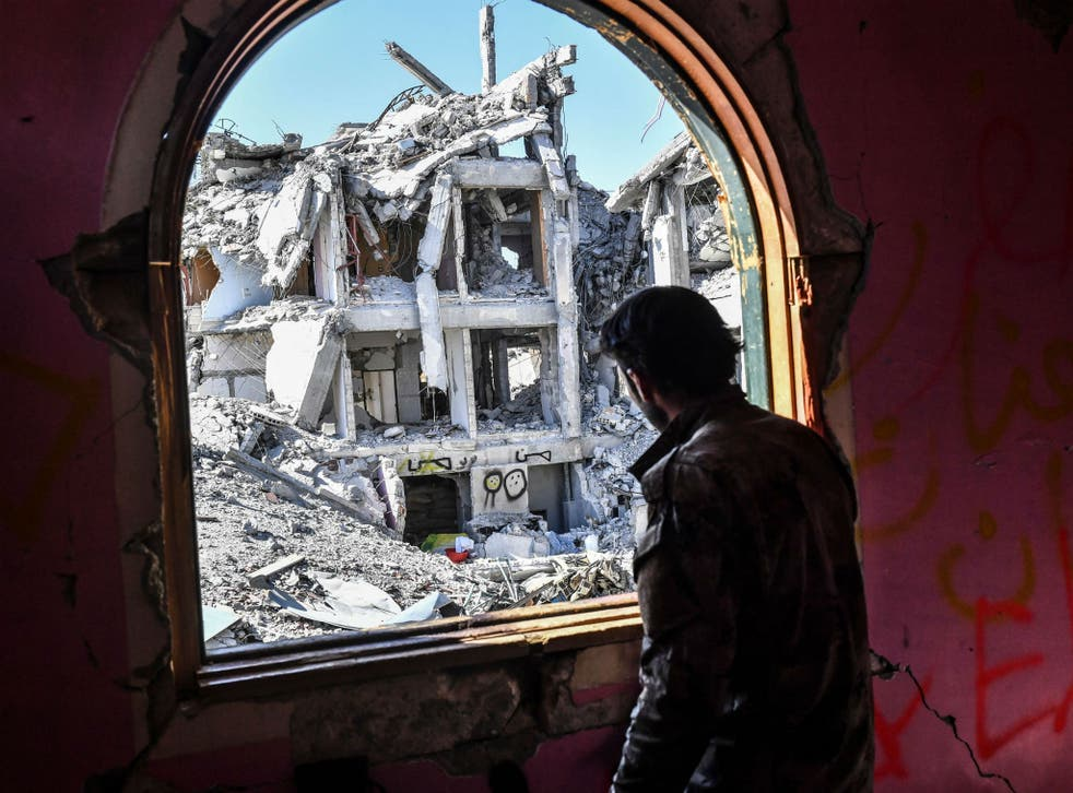 A member of the SDF looks at the destruction, during the battle for the city