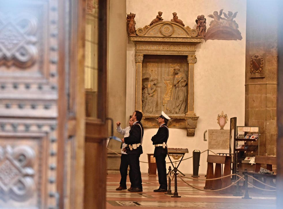 Police stand inside Santa Croce Basilica where a 52-year-old Spanish tourist was killed after being struck by masonry