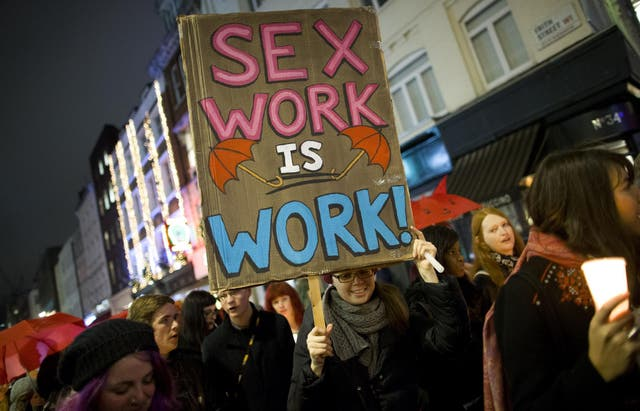 A protester holds a placard while marching through London after a candle-lit vigil to mark the international day to end violence against sex workers