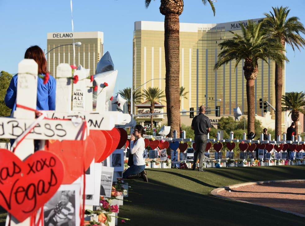 A woman prays beside 58 white crosses for the victims of a mass shooting, on Las Vegas Strip just south of the Mandalay Bay hotel