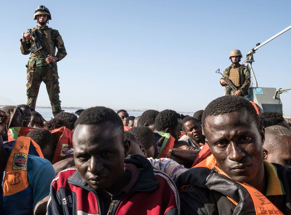 Members of the Libyan coastguard stand on a boat while detaining 147 migrants attempting to reach Europe off the coastal town of Zawiyah on 27 June 2017