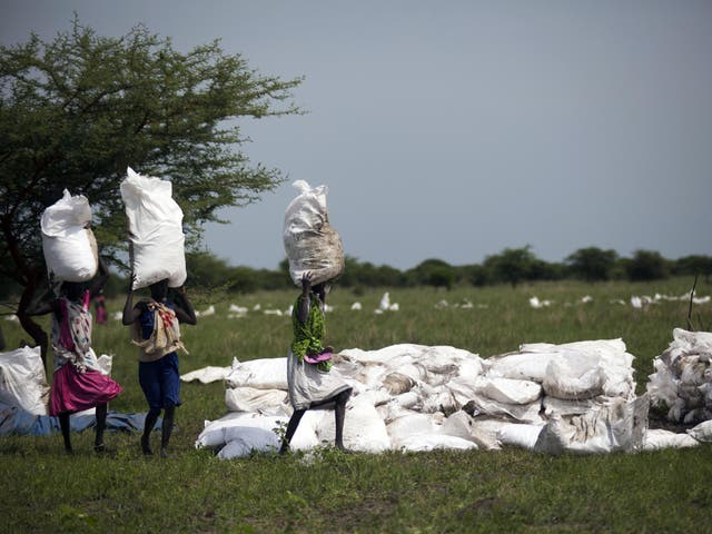 Women carry sacks of food, airdropped by the World Food Programme in South Sudan